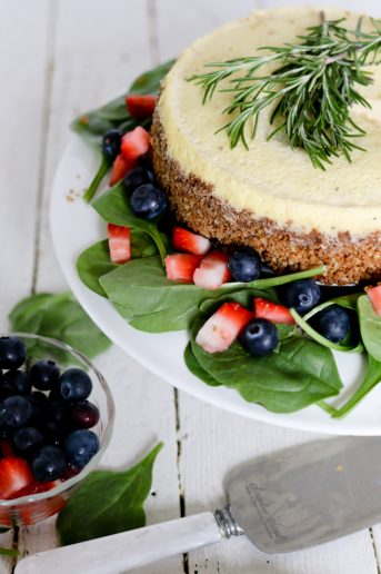 Top shot of a blue cheese cheesecake on a serving plate dressed with fruit