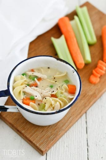 Creamy chicken noodle soup in a bowl on a wooden work surface