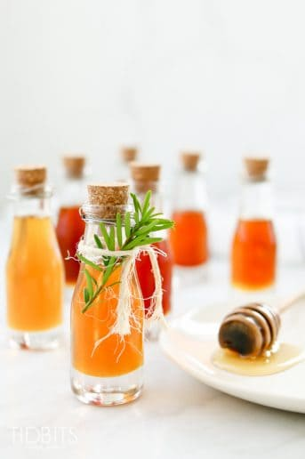 Bottles of infused honey on a white background