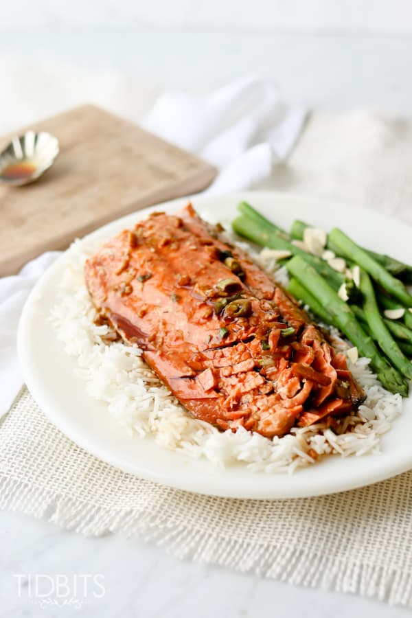 Teriyaki salmon served on a white plate with rice and vegetables