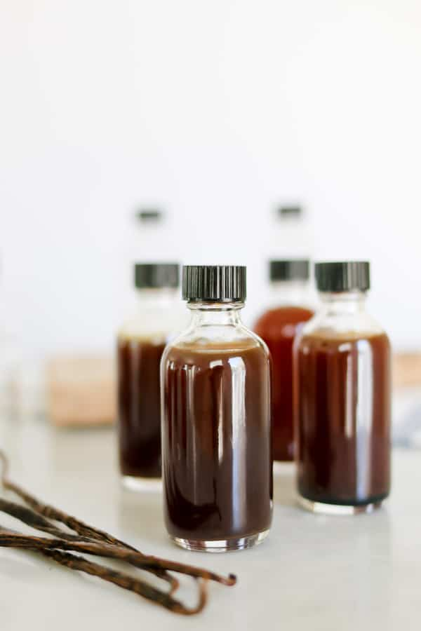 Bottles of homemade vanilla extract on a white background