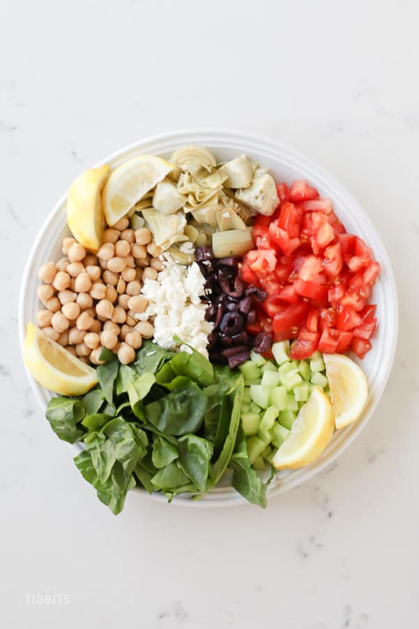 Ingredients for mediterranean brown rice in a white bowl
