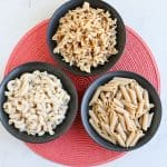Three bowls of pasta on a red mat