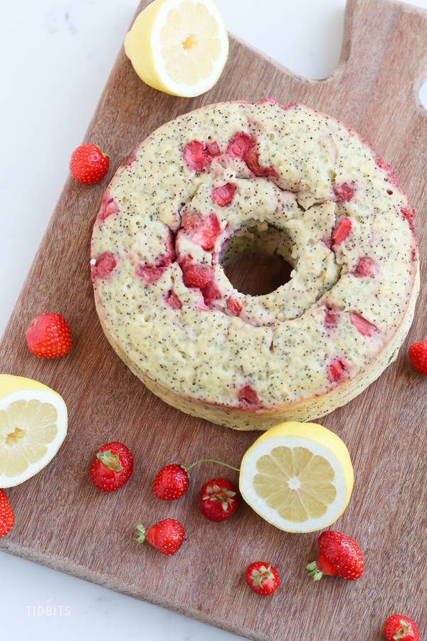 A top down shot of a strawberry lemon poppyseed breakfast cake on a wooden chopping board