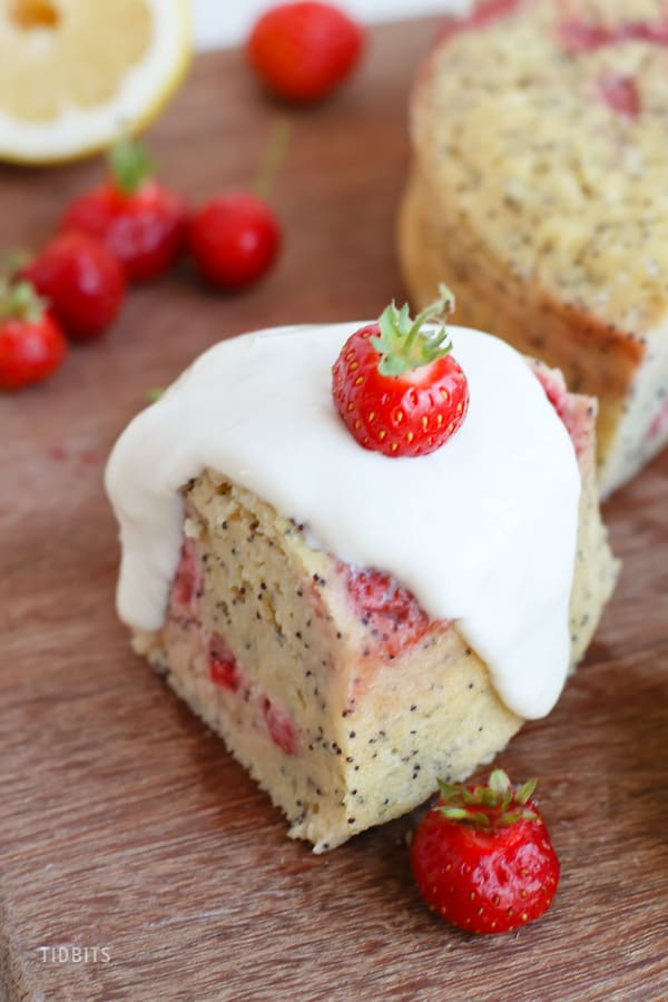 Close up of a slice of breakfast cake next to fresh strawberries