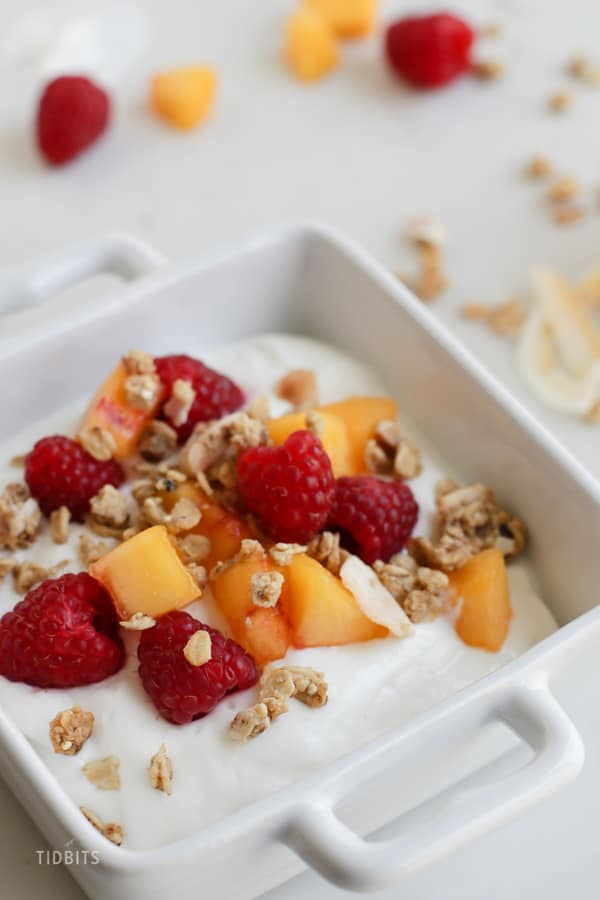Instant Pot yogurt in a bowl with peaches, raspberries and granola