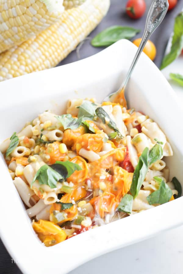 A bowl of Sweet Corn and Tomato Pasta with a fork
