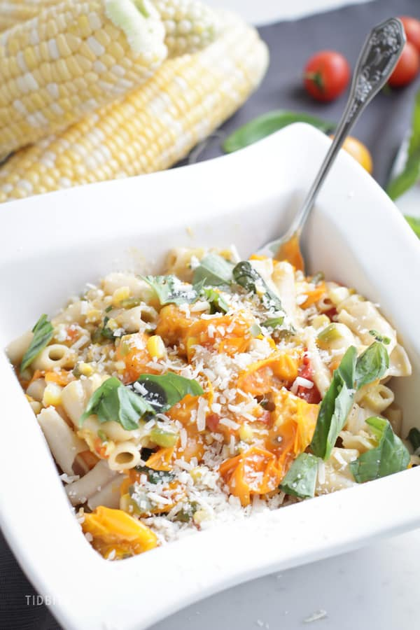 A close up of Sweet Corn and Tomato Pasta in a square white bowl