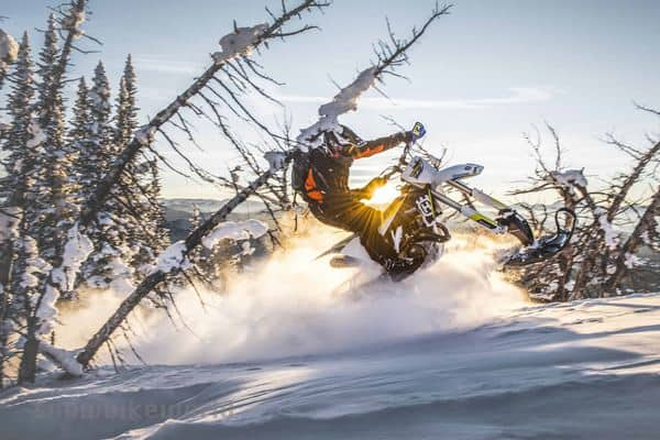 A motorbike rider jumping in snow