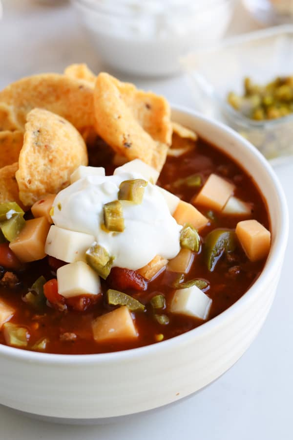 chili in a white bowl topped with sour cream, chips and cheese