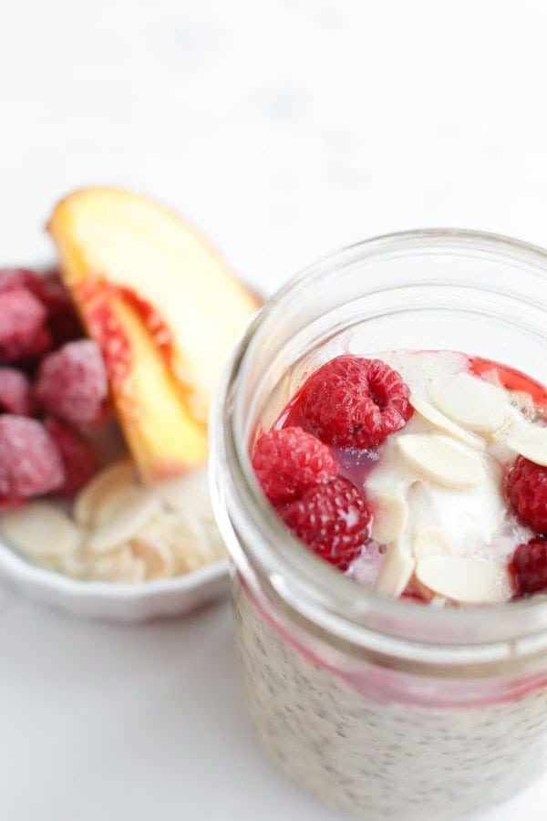 Mason jar steel cut oats with peaches and raspberries and cream on top