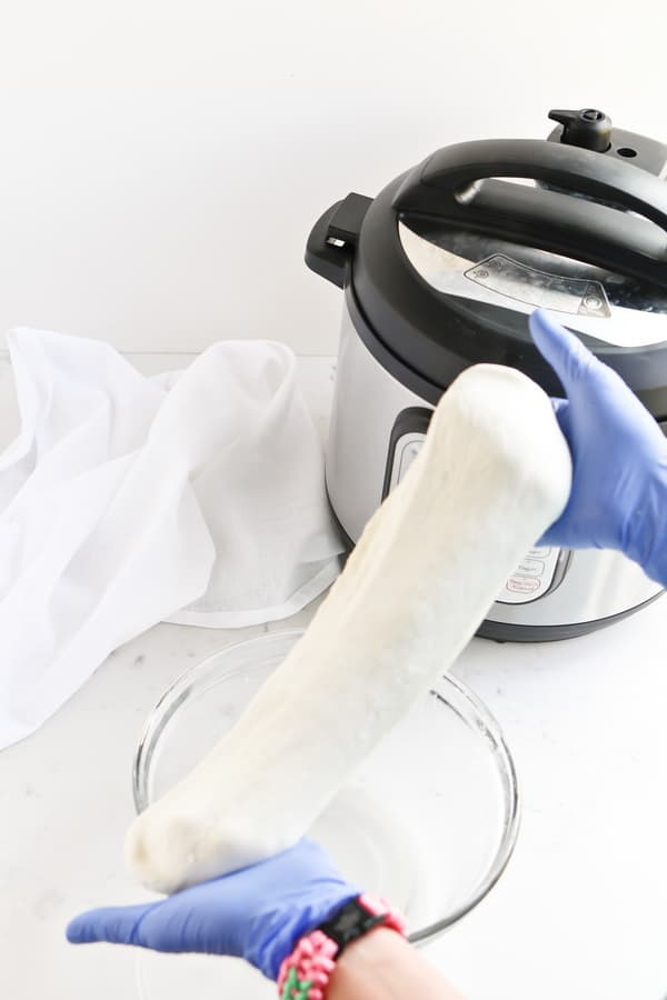 Hands stretching pressure cooker mozzarella
