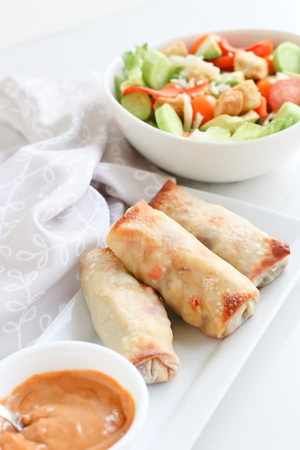Pepperoncini Beef Egg Rolls on a white serving plate with dip