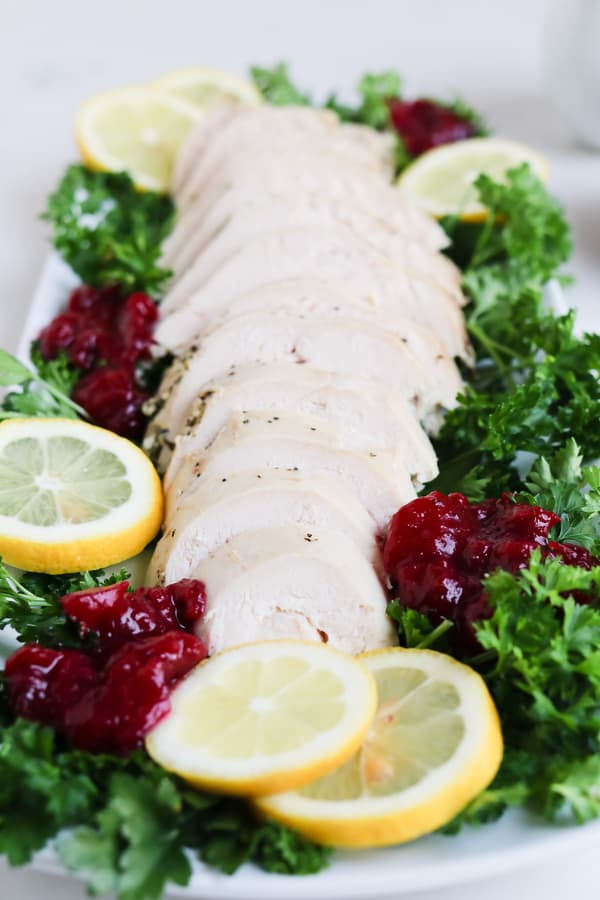 Sliced Turkey on a plate with parsley, lemons, and cranberries