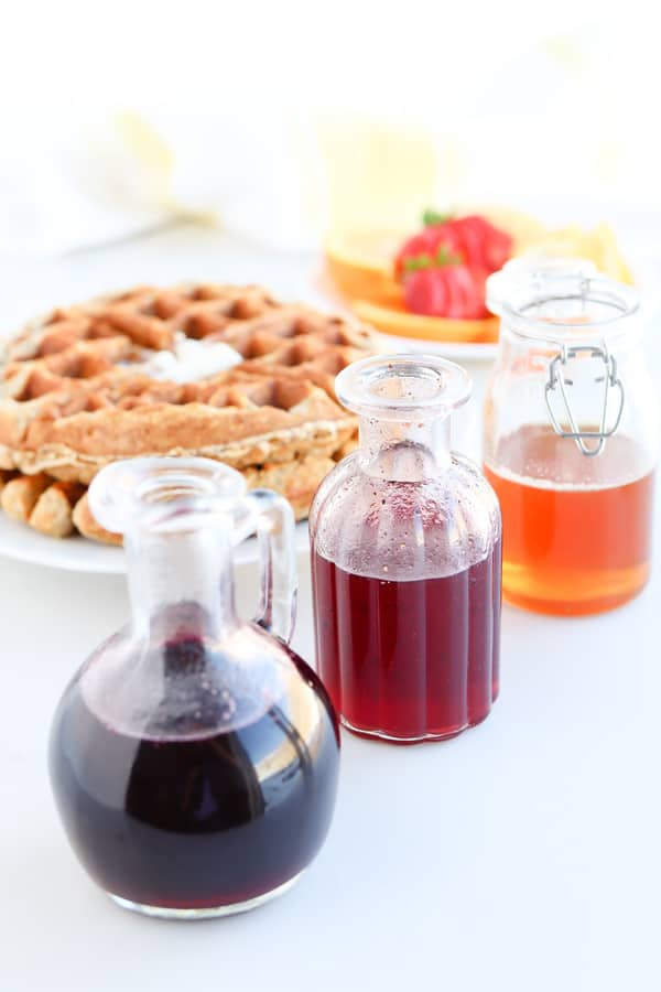 Pressure Cooker Infused Honey Syrup in jars next to a waffle