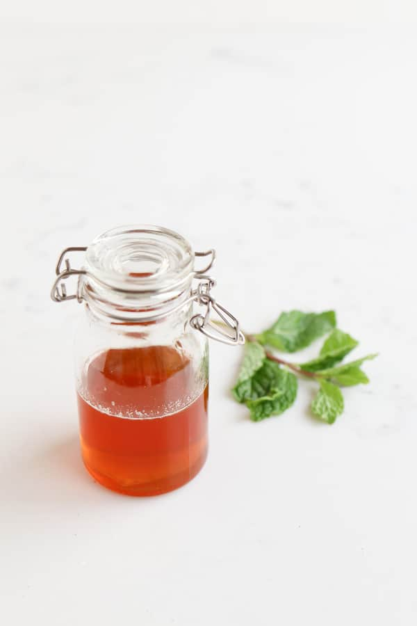 A jar of honey next to a mint leaf
