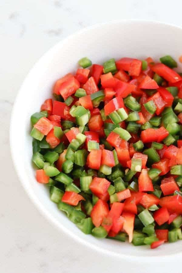 Diced red bell peppers and jalapenos in a white bowl
