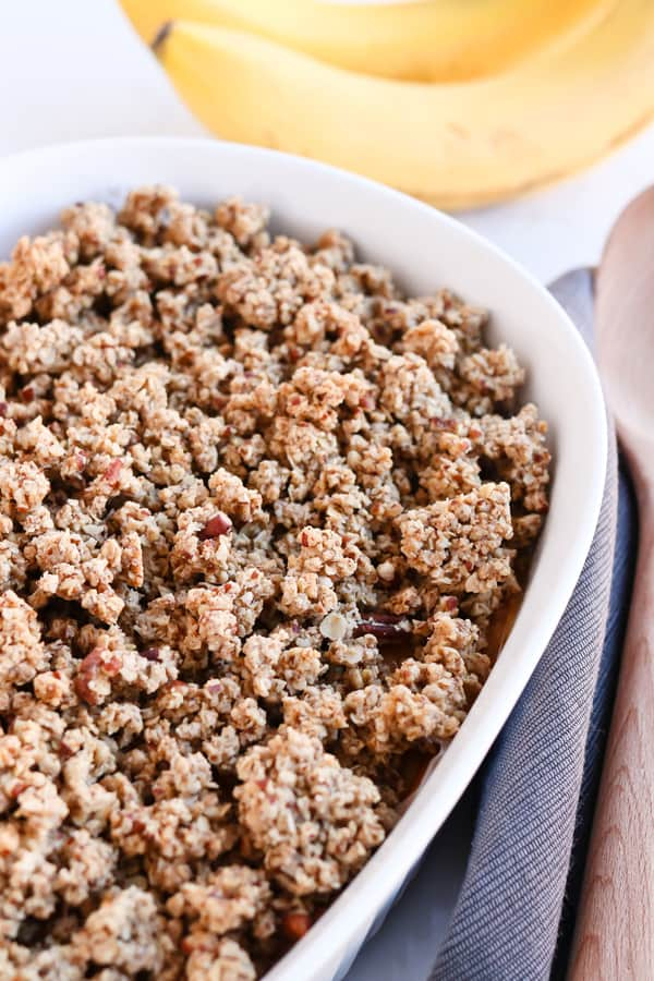 Sweet Potato Casserole with a pecan crumble in a white dish