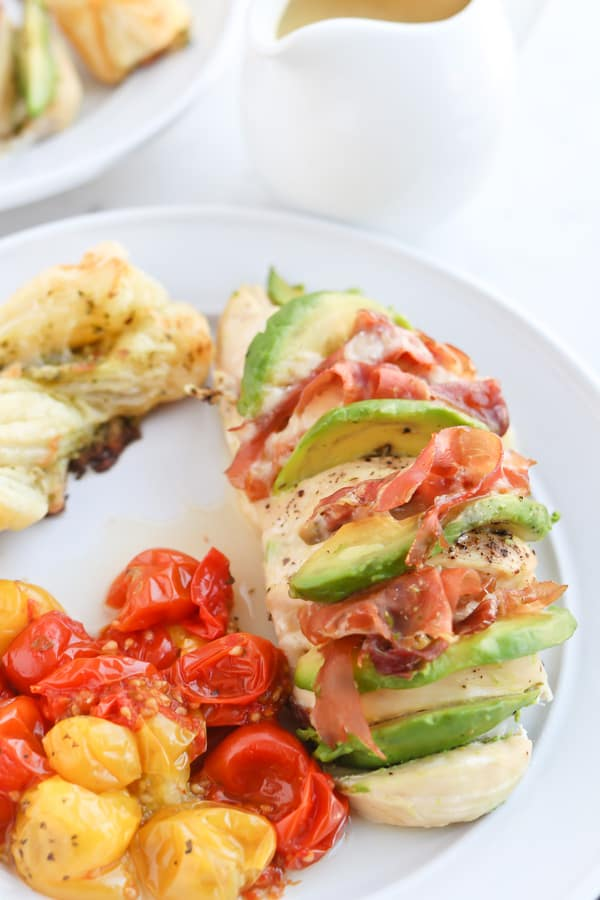 Hassleback chicken on a serving plate with tomatoes