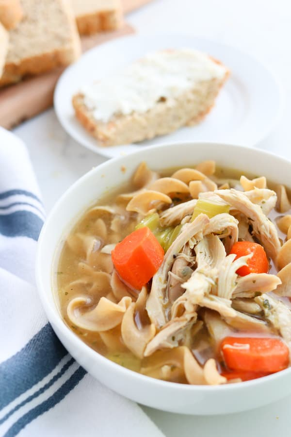 A bowl of chicken noodle soup with bread in the background