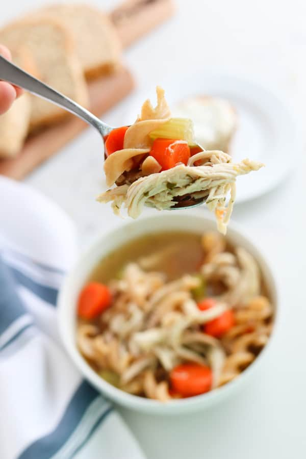 A spoon of chicken noodle soup being held towards the camera