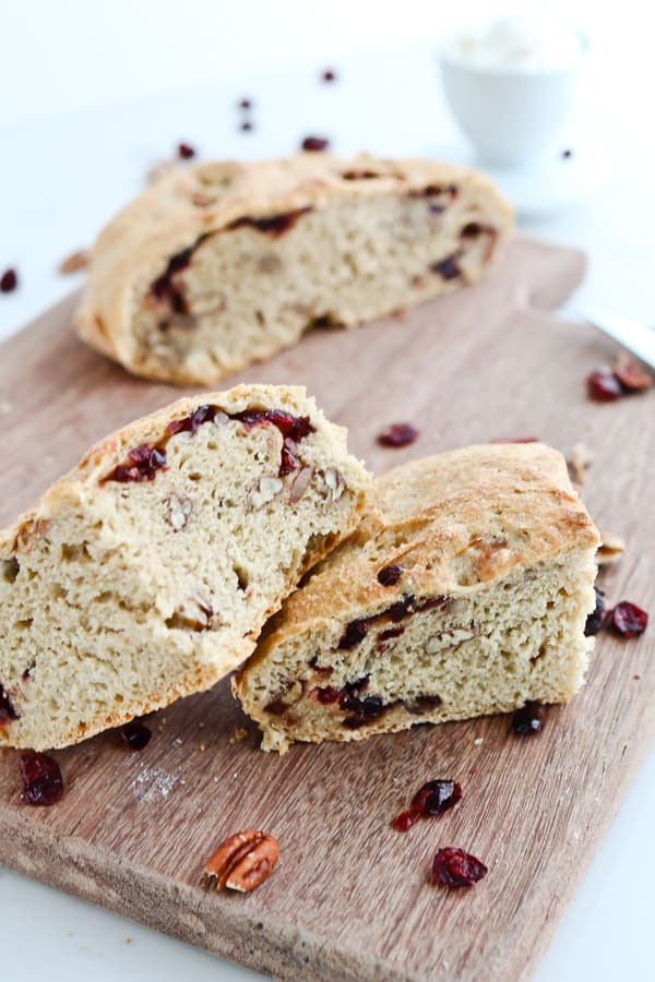 Cranberry pecan crusty bread cut into wedges on a wooden board