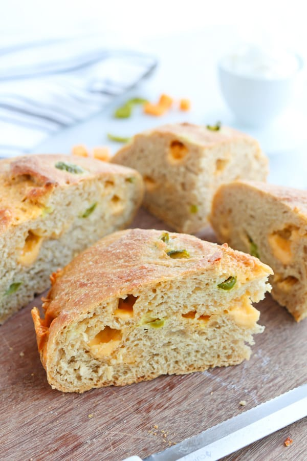 Slices of jalapeno cheddar crusty bread cut in slices on a wooden board