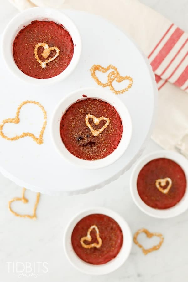 Top down shot of red velvet creme brulee in ramakins on a white background