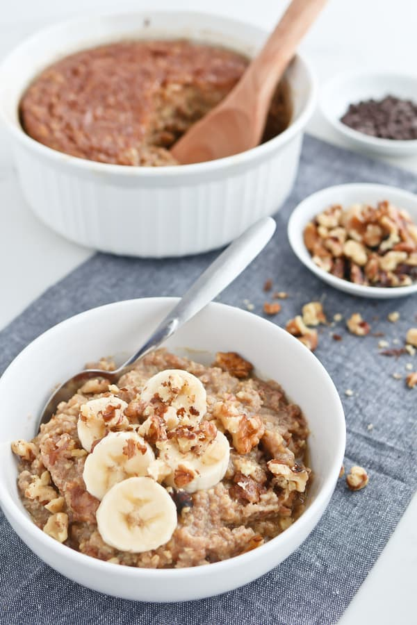 Steel cut oats in a white bowl topped with banana