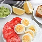 Pressure cooker boiled eggs and fresh tomatoes sliced on a plate