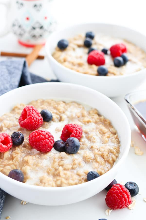 Two bowls of Pressure Cooker Maple Cinnamon Oatmeal topped with berries
