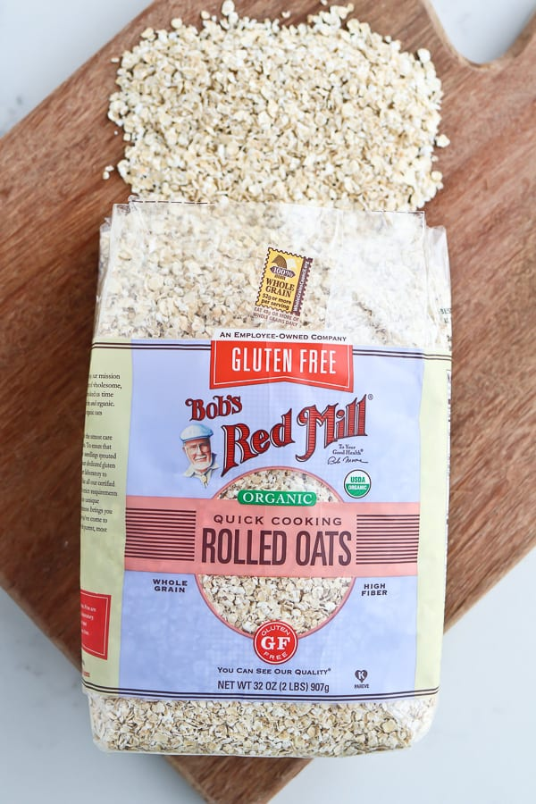 Rolled oats in packaging on a wooden chopping board