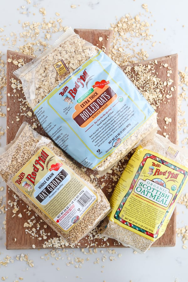 Three packages of oats on a wooden board