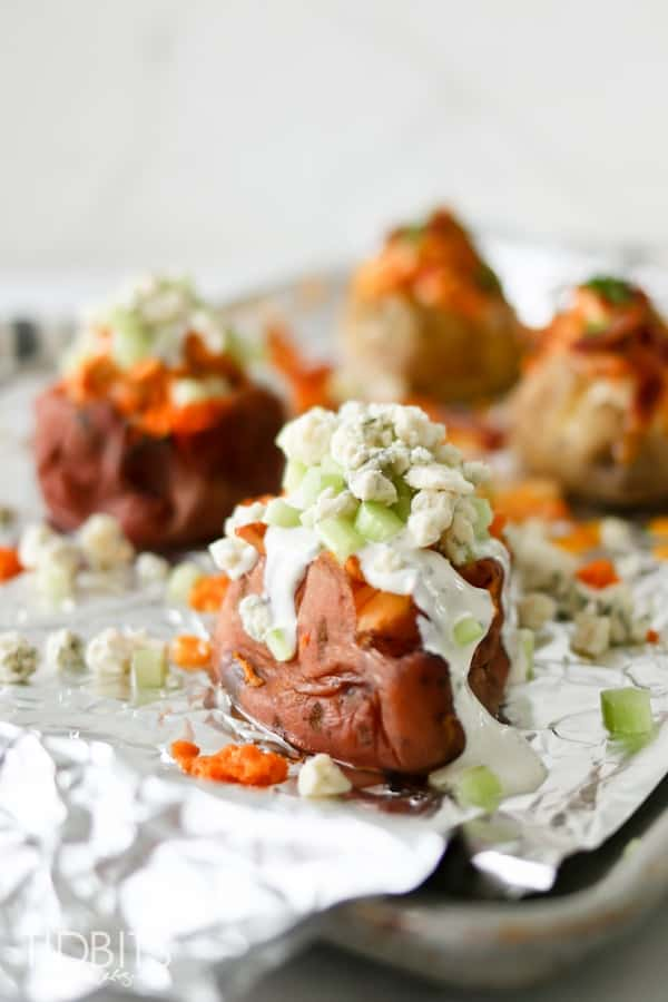 Buffalo chicken stuffed potatoes on a baking sheet