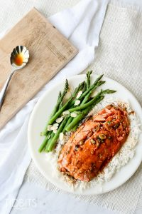 Top shot of Teriyaki Salmon on a white plate served with greens