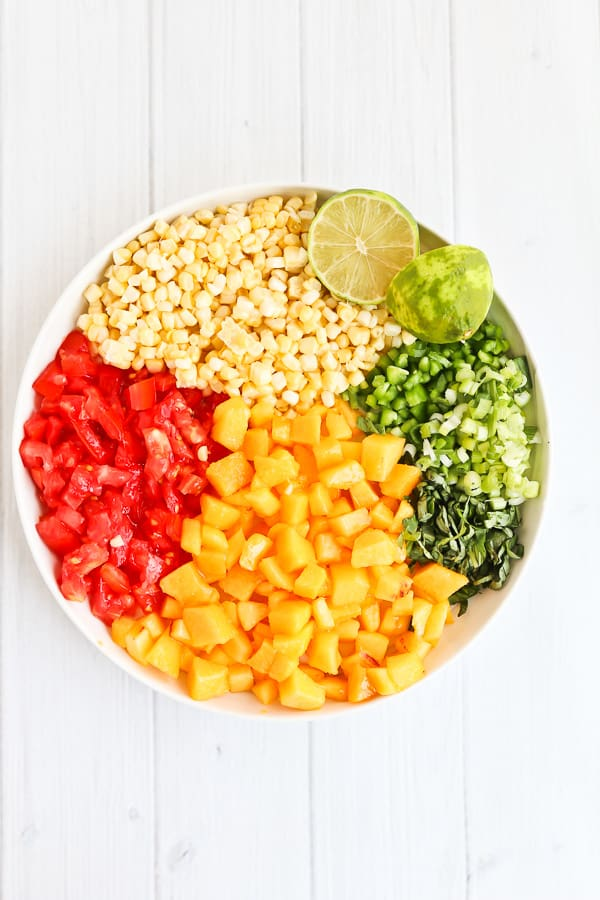 corn, tomatoes, peaches, basil and green onions on a white plate