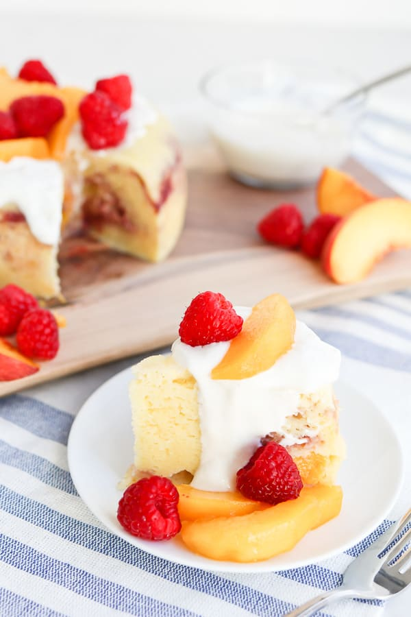 Slice of Raspberry Peach Cake with yogurt sauce on a white plate