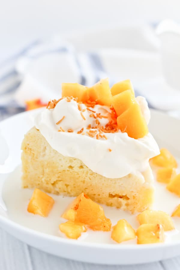 tres leches cake with peaches and cream in a bowl