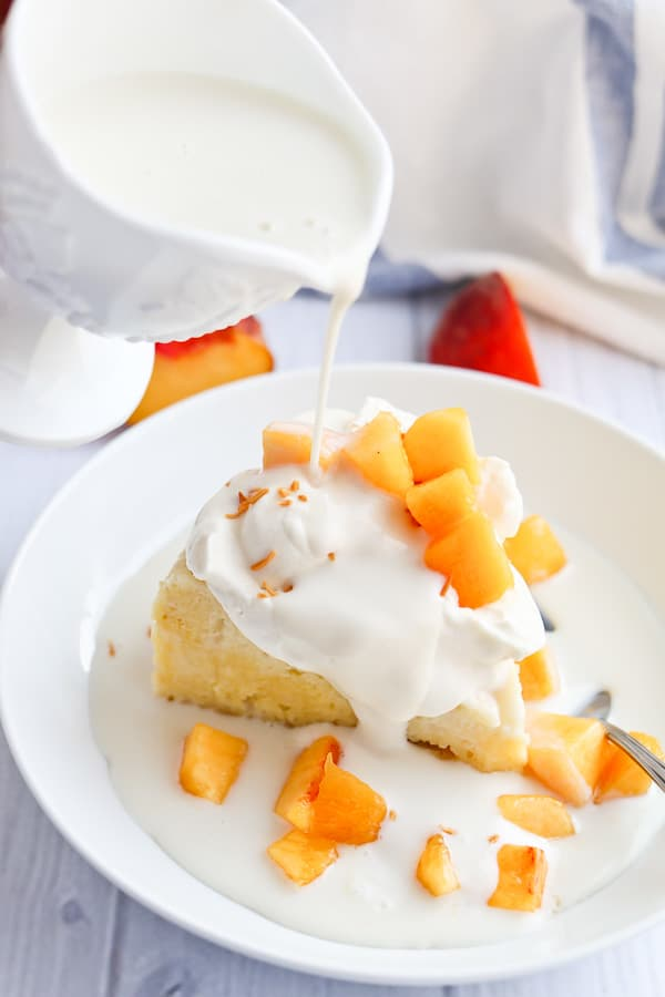 tres leches cake with peaches and cream and sweet milk drizzle