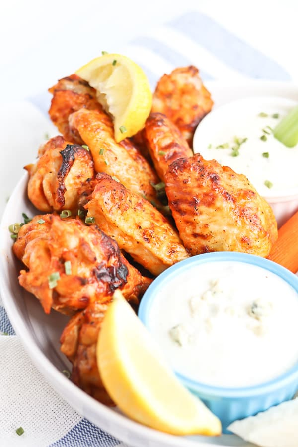 chicken wings on a plate with carrots and celery