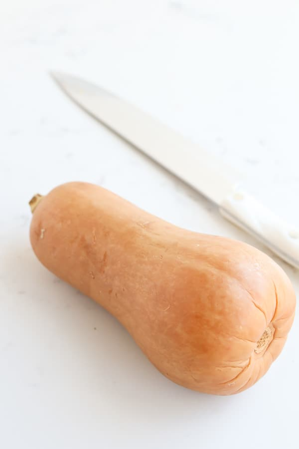 Butternut squash on a white surface with a knife