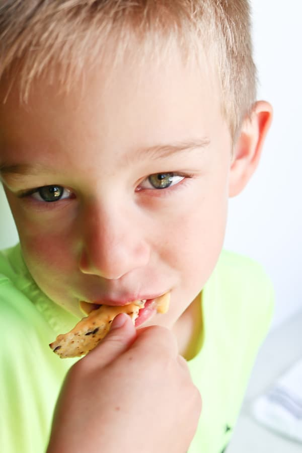 Boy eating a chip with cheese sauce