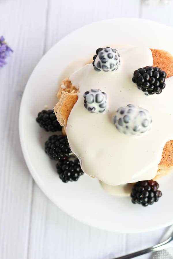pancakes with cashew cream sauce and blackberries on a plate
