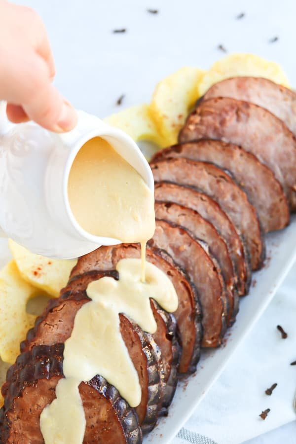 Instant Pot Ham on a white plate with mustard sauce