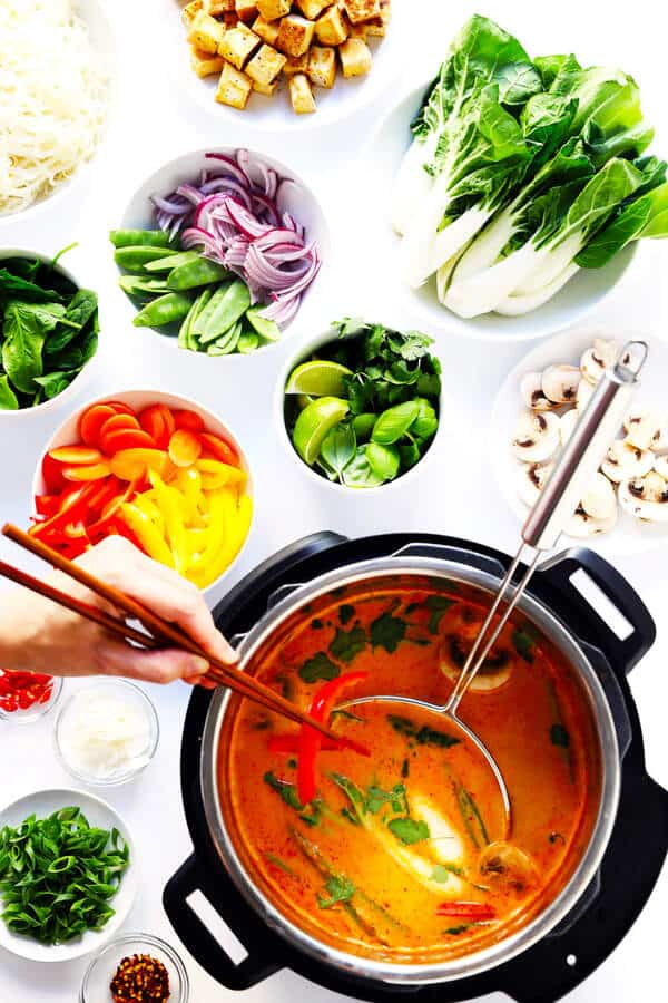 pot of thai broth with various toppings