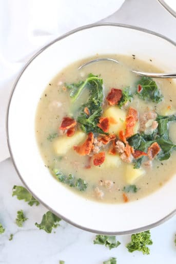 sausage, potato, kale soup in a white bowl