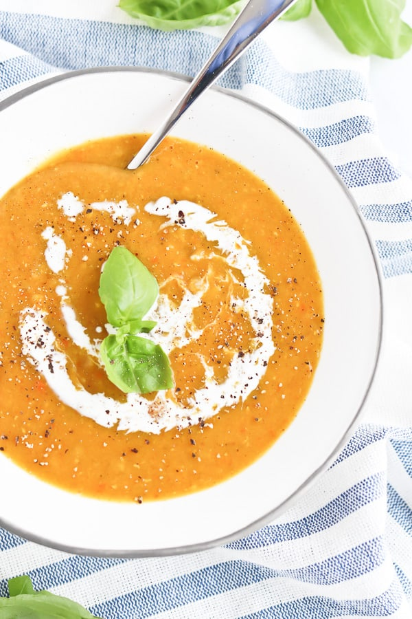 red lentil soup in a white bowl with cream and basil