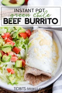 Burrito with white sauce and cheese next to a salad of lettuce, tomatoes, and avocado