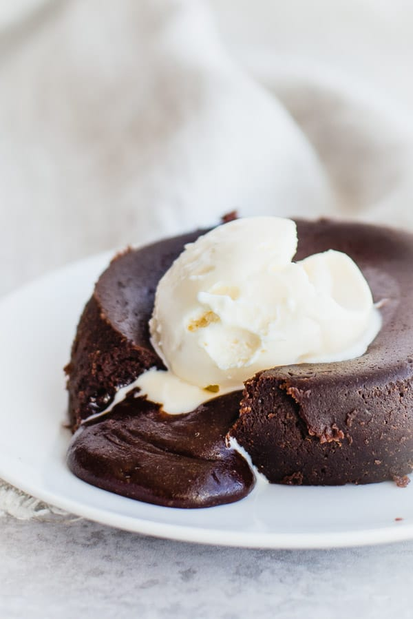 Chocolate lava cake on a white plate with ice cream