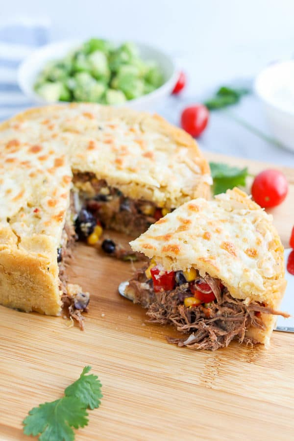 Slice of Tamale pie with meat and veggies on a wood cutting board
